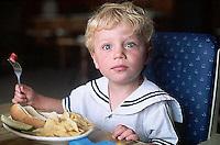 September 1994, Paris, France --- Tunui Franken holds a fork and wears a look of surprise after being startled during a meal. Paris, France. --- Image by © Owen Franken/CORBIS