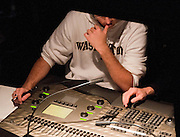 Drama students and teachers adjust sound and lighting control board buttons and sliders at Floyd and Delores Jones Playhouse, Seattle, Washington.