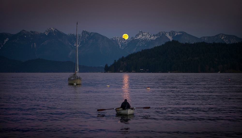 A sailor rows to shore from his boat as the full moon rises in Gibsons, BC. (2015)
