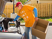 """11 MAY 2020 - DES MOINES, IOWA: JERRY CLUTTS puts food packages into a client's car at a """"no touch"""" emergency food pantry at DSM First Church in Des Moines. The emergency pantry at DSM First Church expanded from distribution one day a week to three days per week after the COVID-19 pandemic forced the closure of many Iowa businesses. Food banks and emergency pantries in Iowa continue to see increased demand for services, even though the governor is reopening the state's economy. Iowa's unemployment rate for April hasn't been released yet, but based on national trends, it is expected to soar to well over 10% from 3.8& in March. COVID-19 infections continue to skyrocket. On Monday, 11 May, the governor announced that 12,373 people tested positive for coronavirus (SAR-CoV-2) and  271 had died.              PHOTO BY JACK KURTZ"""