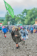 Heroic efforts are made to get through the mud as the rains come down again but generally fail to dampen the spirits  - The 2016 Glastonbury Festival, Worthy Farm, Glastonbury.