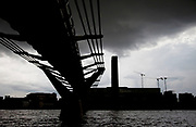 Millennium Bridhe crossing the iver Thames to Tate Modern on a dark, heavy skied day in London.