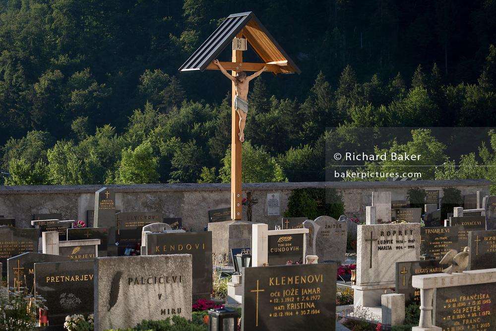 A crucifix looks down on headstones in a rural Slovenian village church, on 18th June 2018, in Bohinjska Bela, Bled, Slovenia.