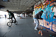 A walk along the River Thames on the Southbank in London. A graffiti artist sprays a new piece. Part of the South Bank Centre known as the under-croft, has been used by the skateboarding community since the early seventies. Originally an architectural dead-spot, it has become a home of British skateboarding. This area is very popular especially on the weekends for Londoners to walk and see different arts, culture and entertainment.