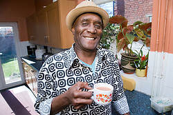 Older man at home in his kitchen drinking a hot drink,