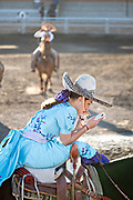 Saray Franco with the legendary Franco family of Charro champions, looks at her mobile phone while waiting for her event during a Mexican rodeo practice session in the Jalisco Highlands town of Capilla de Guadalupe, Mexico. Women participants in the traditional Charreada are called Escaramuza and perform precision equestrian displays riding sidesaddle and garbed in Adelita dress.