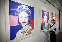 © Licensed to London News Pictures. 14/09/2012. LONDON, UK. A member of Sotheby's staff adjusts one of the four prints that make up Andy Warhol's 'Reigning Queens: Queen Elizabeth II (Royal Edition)' (1985) est. £100,000-150,000 as the New Bond Street auction house prepares for a sale of 'Old Master, Modern and Contemporary Prints'. The auction, set to take place on the 19th of September 2012, features nearly 200 masterful works artists including Andy Warhol, Lucian Freud and Francis Bacon. Photo credit: Matt Cetti-Roberts/LNP