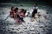 China, Guizhou Province Southern China, Conjiang City, Kids playing down by the river bank, evening.