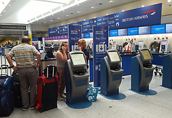 "Passengers at the British Airways check-in desk at Gatwick Airport. The airline says it has cancelled all flights leaving from Heathrow and Gatwick for the rest of today because of a ""major IT system failure""."