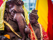 """07 SEPTEMBER 2014 - BANGKOK, THAILAND: Statue of Ganesh, the """"Overcomer of Obstacles"""" with his mother, Shiva at the Ganesh Festival in Bangkok. Ganesh Chaturthi, also known as Vinayaka Chaturthi, is a Hindu festival dedicated to Lord Ganesh. It is a 10-day festival marking the birthday of Ganesh, who is widely worshiped for his auspicious beginnings. Ganesh is the patron of arts and sciences, the deity of intellect and wisdom -- identified by his elephant head. The holiday is celebrated for 10 days, in 2014, most Hindu temples will submerge their Ganesh shrines and deities on September 7.     PHOTO BY JACK KURTZ"""