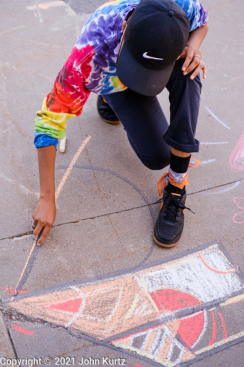 19 JUNE 2021 - DES MOINES, IOWA: An artist chalks the sidewalk during the Juneteenth celebration in downtown Des Moines. Juneteenth marks the day, after the Civil War, that slaves in Texas learned that they were free. Slaves in Texas were freed when Union army General Gordon Granger captured Galveston, Texas, and announced General Order No. 3 proclaiming freedom for slaves held in Texas. Juneteenth has been celebrated in the Black community for more than 100 years. On June 17, 2021, President Joe Biden signed the Juneteenth National Independence Day Act making it a federal holiday.       PHOTO BY JACK KURTZ