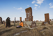 A traveler talks with local Armenian woman at Noratus cemetery, a historic cemetery that dates back to the medieval period, located 90 kilometers north of Yerevan, Armenia. (September 25, 2016)