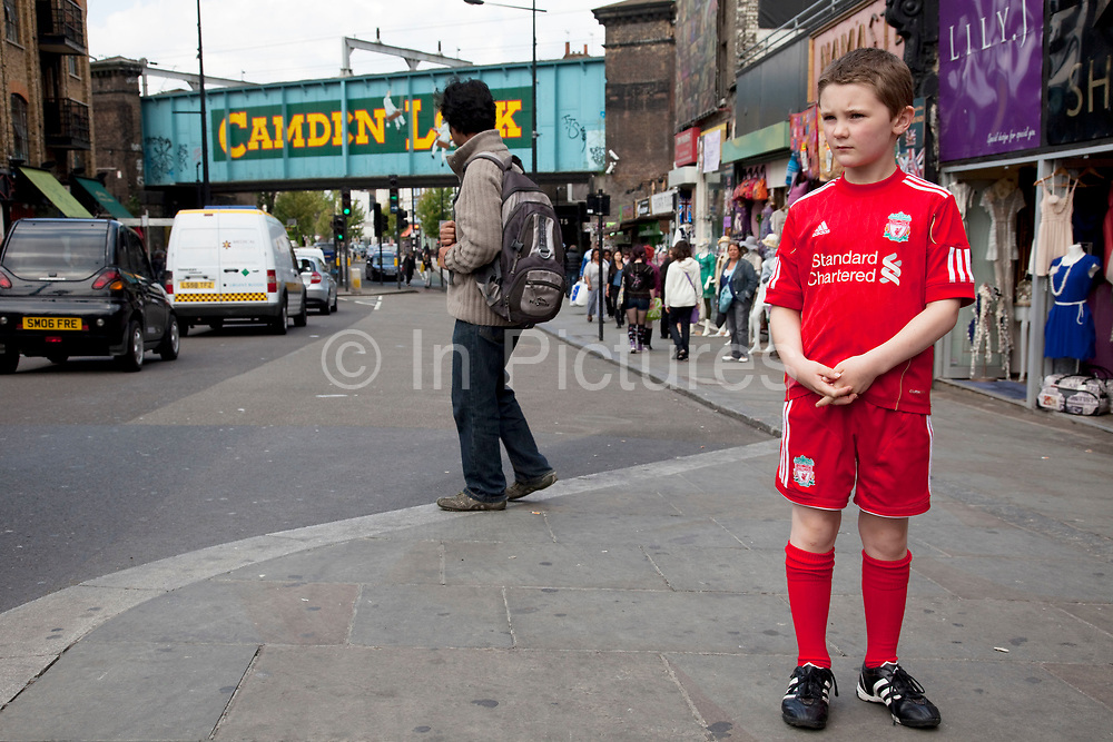 LONDON, ENGLAND, UK, JUNE 11TH 2011. Kiefer (8, wearing a red Liverpool Football Club kit) spending a day out in Camden Town, North London. Here they are walking near to the famous sign for Camden Lock on the railway bridge. Louise (his mother) is on various benefits to help support her family income, and housing, although recent government changed to benefits may affect her family drastically, possibly meaning they may have to move out of London. Louise Ryan was born on the Wirral peninsula in 1970.  She moved to London with her family in 1980.  Having lived in both Manchester and Ireland, she now lives permanently in North London with her husband and two children. Through the years Louise has battled to recover from a serious motorcycle accident in 1992 and has recently been diagnosed with Bipolar Affective Disorder. (Photo by Mike Kemp/For The Washington Post)