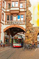A tram goes under the McDonald's built into Martinsgate (Martinstor), Freiburg, Baden-Württemberg, Germany