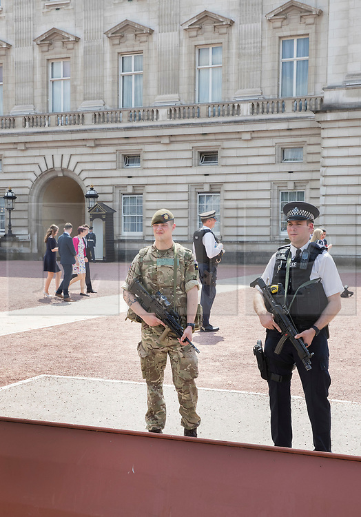 © Licensed to London News Pictures. 24/05/2017. London, UK. A soldier stands with policeman on guard duty at Buckingham Palace. The terrorism threat level has been raised to critical and Operation Temperer has been deployed. 5,000 troops are taking over patrol duties under police command. Photo credit: Peter Macdiarmid/LNP