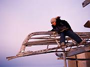 Seven-year-old Ralph Aveoganna playing on Umiak frame, Inupiat village of Wainwright, Arctic Coast of Alaska.