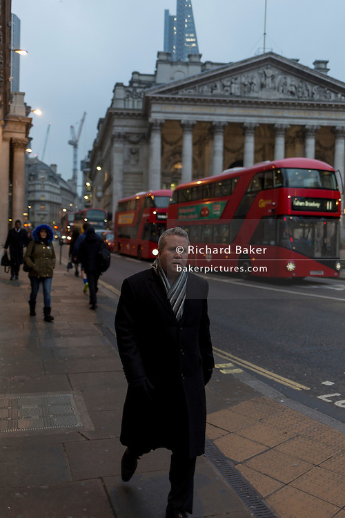 A worried-looking commuter walks past the neo-Roman pillars of Royal Exchange and buses on 9th February 2017, in the City of London, England.