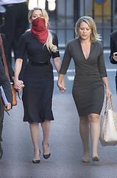 © Licensed to London News Pictures. 07/07/2020. London, UK. US actor Amber Heard (red facemask) arrives at The High Court in Central London holding hands with Australian lawyer Jennifer Robinson (R). Johnny Depp's libel trial against The Sun newspaper is due to take place over the next three weeks over allegations he was violent and abusive towards his ex-wife Amber Heard. Photo credit: Peter Macdiarmid/LNP