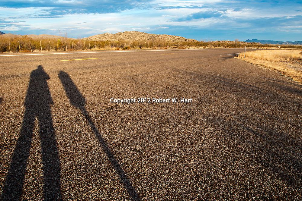 Texas photographer, Robert Hart, casts a long shadow across Hwy 385 south of Marathon, Texas, near the entrance to Big Bend National Park.<br /> <br /> ©2014 Robert W. Hart