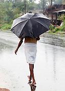 Man walking the streets through the monsoon rains, Cochin, Kerala, India.