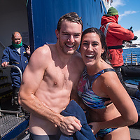 """A young couple smiles after completing the """"polar plunge"""" in the icy waters off of Brown Bluff in Antarctica."""