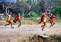 BURMA (MYANMAR) Shan State, Nyaungshwe, Inle Lake. 2003. An afternoon football match between monks, some sharing shoes or not wearing them at all.