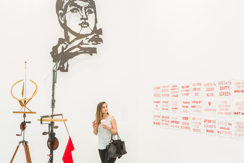 "New York, NY - 6 May 2016. Frieze New York art fair. A visitor takes in the exhibits in the Marian Goodman Gallery, which has outlets in New York, London and Paris. The piece with the red text is Wiliam Kentridge's ""In Mockery of Progress."""