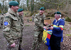 The Duke of Sussex receives a gift of a rugby shirt and a picture from former Marine Yorkie Malone during a visit to 42 Commando Royal Marines at their base in Bickleigh.