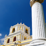 In the foreground to the right is a white faux-marble column with a bust of Fray Bartolome de las Casas. In the background is part of the distinctive yellow and white exterior of the Iglesia y Convento de Nuestra Senora de la Merced in downtown Antigua, Guatemala.