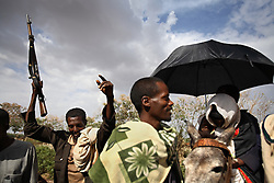 Leyualem Mucha, 14, is greeted with gunshots as she arrives at the home of her new husband in the Amhara Region, Ethiopia on May 23, 2007. Leyualem had never met her husband before her wedding day, yet sumitted as they bound her in the white wedding cloth. The men later said it was placed over her head so she would not be able to find her way back home, should she want to escape the marriage.