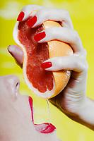 beautiful caucasian woman squeeze and drink grapefruit juice studio on yellow background