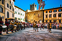 """""""Archidado Cortona flag flyers""""…<br /> <br /> Every year, a procession of 300 or more people wearing wonderful medieval costumes, as well as many riders on their horses, parade through Cortona's historic center. The competition known as the Giostra dell'Archidado commemorates the wedding of Francesco Casali, Lord of Cortona, and the noblewoman Antonia Salimbeni of Sienna, which took place in 1397. The crossbowmen from Cortona's five quarters, """"Quintieri"""", compete for a golden arrow. The contest is held in Piazza Signorelli.  Flag throwing (or flag tossing) is often a major part of the historical costume festivals that are one of the great attractions of Tuscany and, indeed, of all Italy. The performers, known as Sbandieratori, usually young men but with an increasing number of young ladies taking part, dress in medieval costume and are usually accompanied by drummers (Tamburi) and sometimes trumpeters (Trombettieri). Skills range from good to truly excellent. The younger participants engage in synchronized flag waving through tossing and catching their own flags, while the truly skilled carry out amazing and beautiful exercises involving simultaneously throwing two flags to two partners in their team.  I was fortunate to arrive in Cortona from Roma on Sunday, the last day of the festival."""