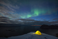 Yellow tent on snow covered mountain peak of Veggen with Northern Lights - Aurora Borealis in sky above, Lofoten Islands, Norway