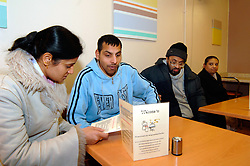 Group of men with learning disabilities in cafe with carer; Bradford; Yorkshire UK