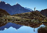 A trekking guide plays the Andean flute and reflects in a pond in the Cordillera Vilcabamba, Andes mountains, along the Inca Trail, Peru, South America. Our multi-talented guide Wilbert attracted us higher with his Andean flute. He played several more instruments, spoke eight languages, earned a Ph.D. in Anthropology from a Peruvian university, and had a playful sense of humor.