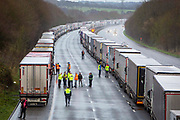 Drivers mingle out of their cabs as their freight lorries line up in queues contained in Operation Stack on the M20 motorway at Ashford, Kent, United Kingdom on the 23rd of December 2020. Truck drivers have been waiting in operation stack on the M20 motorway for over 48 hours now, France closed it's boarders with the UK after a new faster spreading strain of the COVID-19 virus broke out in Kent.