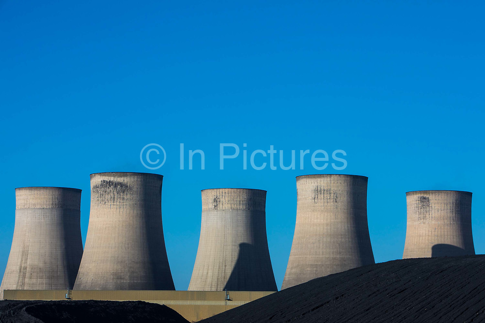 A huge pile of black coal next to the cooling towers of Ratcliffe-on-Soar coal fired power station, owned and operated by Uniper at Ratcliffe-on-Soar on the 26th of February 2021 in Nottinghamshire, United Kingdom. The plant emits 8–10milliontonnes of CO2 annually. It has a generating capacity of 2,116MW,  enough electricity to meet the needs of approximately 2million homes.