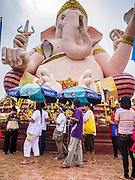 """29 SEPTEMBER 2012 - NAKORN NAYOK, THAILAND:  Thai Buddhists process around a statue of Ganesh while they carry offerings to Ganesh during observances of Ganesh Ustav at Wat Utthayan Ganesh, a temple dedicated to Ganesh in Nakorn Nayok, about three hours from Bangkok. Many Thai Buddhists incorporate Hindu elements, including worship of Ganesh into their spiritual life. Ganesha Chaturthi also known as Vinayaka Chaturthi, is the Hindu festival celebrated on the day of the re-birth of Lord Ganesha, the son of Shiva and Parvati. The festival, also known as Ganeshotsav (""""festival of Ganesha"""") is observed in the Hindu calendar month of Bhaadrapada, starting on the the fourth day of the waxing moon. The festival lasts for 10 days, ending on the fourteenth day of the waxing moon. Outside India, it is celebrated widely in Nepal and by Hindus in the United States, Canada, Mauritius, Singapore, Thailand, Cambodia, Burma , Fiji and Trinidad & Tobago.     PHOTO BY JACK KURTZ"""