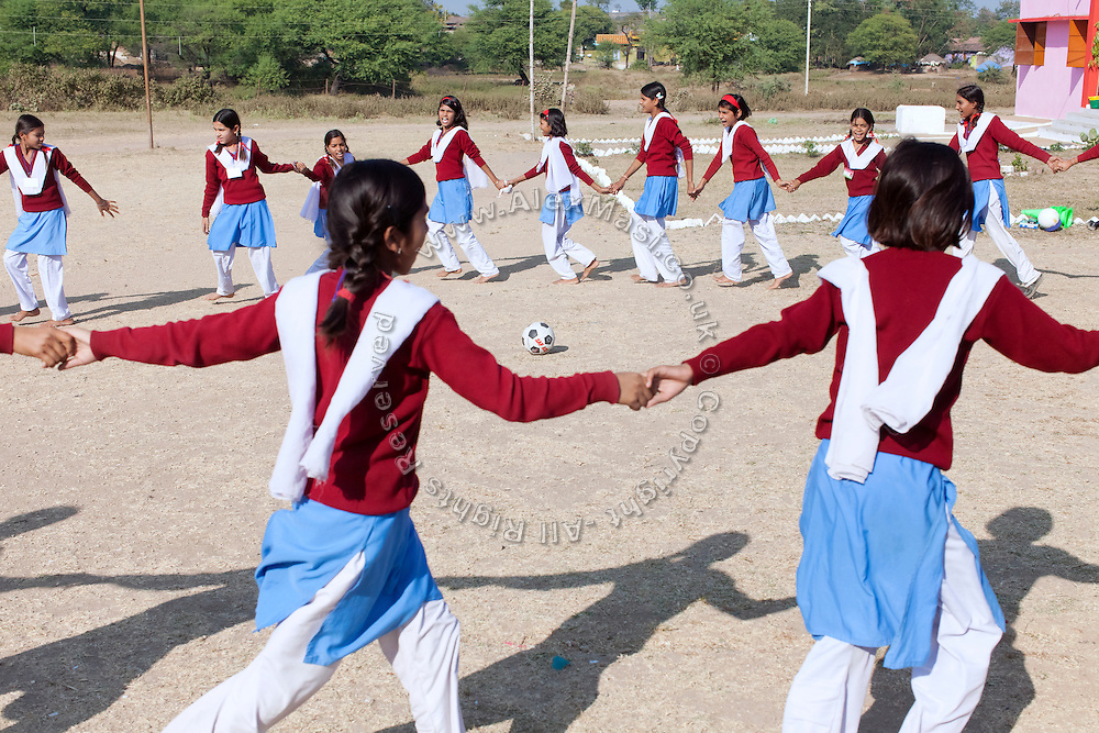 Ritu Gaur, 13, (top left near ball) is playing in a circle with other pupils in front of the Jamoniya Tank Girls Hostel, near Sehore, Madhya Pradesh, India, where the Unicef India Sport For Development Project has started in 2012. Covering 313 state-run girls' hostels and 207 mixed hostels in Madhya Pradesh, the project ensures that children from Scheduled Tribes (ST) and others amongst the poorest people in India, can easily access education and be introduced to sports. Field workers from Unicef also oversee their nutrition and monitor the overall conditions of each pupil.