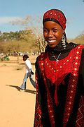 Israel, Negev, Young Bedouin girl in traditional clothes Facing and smiling at camera