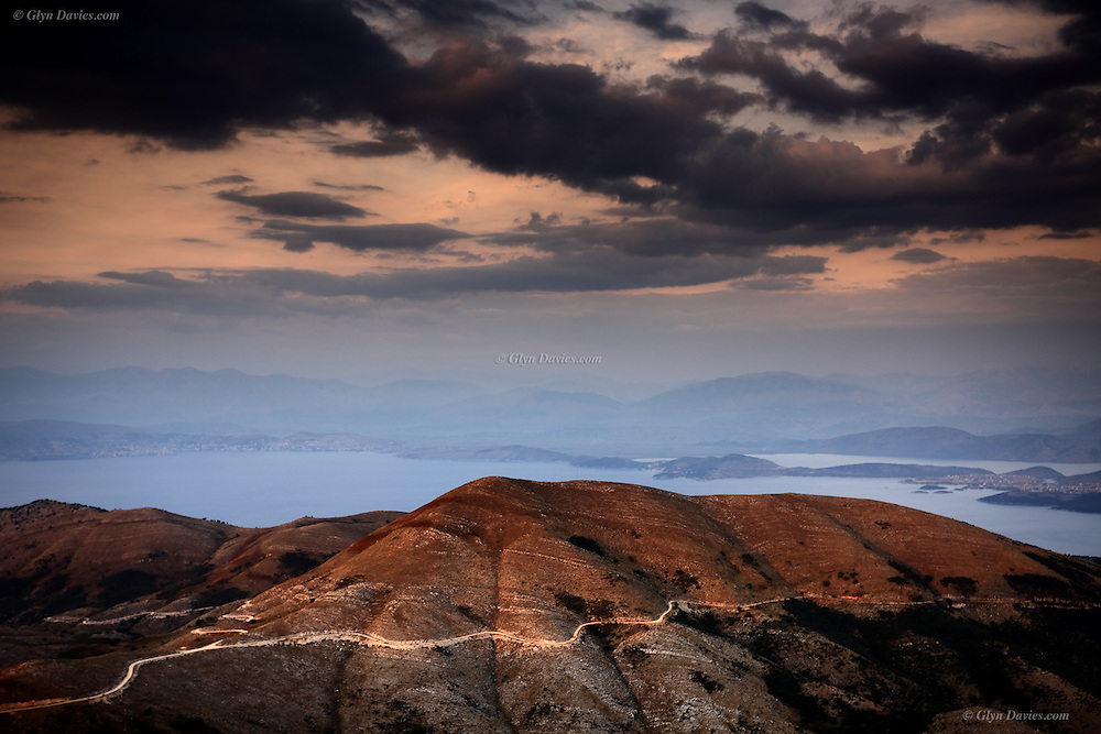 Looking towards Albania from the Mount Pantokrator Monastery on Corfu's highest peak. The light was very soft and the sun watery but a warm glow spread across the hills, more and more intensely as the sun set. The whole time I was there, I couldn't get over how close Albania seemed, here in the UK there is - the UK! But in Corfu I was fascinated by 'notions' of borders, that by sailing a yacht in the sunshine across a short stretch of water from where tourists are swimming that I end up in another country for which I would need to let them know I'd 'arrived'- quite bizarre! I guess it comes from living on a very big island where we can't see much other land anywhere!<br /> <br /> Available as signed, unlimited fine-art rag paper prints, from the largest A1 prints to the smallest A4.