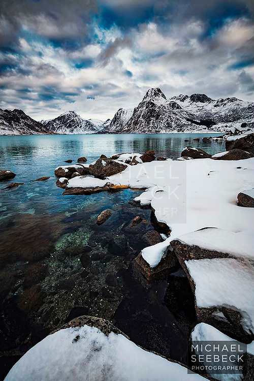 Scattered clouds pass over a spectacular fjord surrounded by mountains, in winter.<br /> <br /> Limited Edition of 125