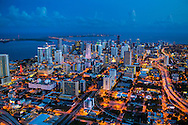 Miami Skyline at twilight with city lights, view looking from northwest to southeast with Biscayne Bay and ocean in the background.