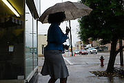 SELMA, AL – MAY 15, 2014: A woman leaving the Super Dollar store in downtown Selma shields herself from the rain. Dallas County has one of Alabama's highest unemployment rates, and in recent months the prospect of a plan to to begin training Kuwaiti pilots in an old military airport is offering new hope for Selma's residents. CREDIT: Bob Miller for The New York Times
