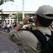 A Police officer films the oncoming protest parade during the Republican National Convention in Tampa, Fla. on Wednesday, August 29, 2012. (AP Photo/Alex Menendez)
