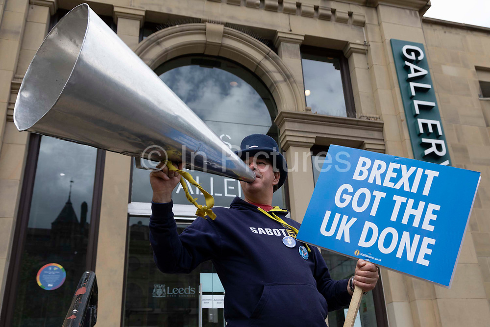 Steven Bray, a British activist commonly known as stop Brexit man, holds up a megaphone and placard reading Brexit Got The UK Done at a protest on 24th June, 2021 in Leeds, United Kingdom. Steven Bray is best known for shouting anti-Brexit slogans during TV broadcasts at Westminster, and wearing a blue outfit adorned with anti-Brexit sentiments.