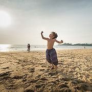 Child flexing his muscle while jumping with joy on a beach.
