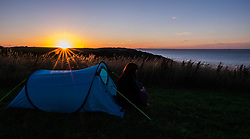 © Licensed to London News Pictures.27/08/15<br /> Saltburn, UK. <br /> <br /> CHARLOTTE PATTISON from Saltburn sits in the entrance of her tent looking out over the north sea at sunset from the upper promenade in Saltburn<br /> <br /> Photo credit : Ian Forsyth/LNP