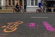 Extinction Rebellion organised protest entitled - No Going Back: Reclaim the Streets! Protesters create pop-up cycle lanes around London (in this case, the Munster Road, Fulham) using stencils and spray paint to endeavour to promote the idea of keeping teh streets 'green' even after the lock down for Coronavirus has ended.