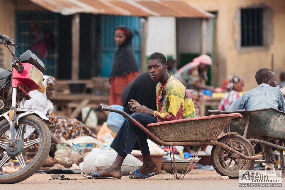 A teenage boy sits in a wheel barrow parked on the road side in Bouake, Cote d'Ivoire on Sunday July 14, 2013.